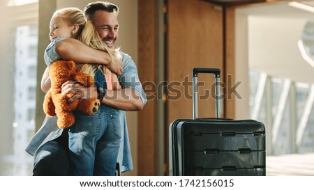 Happy father arriving home and greeting his daughter with a hug. Traveler hugging his kid as he enters the door h Royalty-Free Stock Photo #1742156015