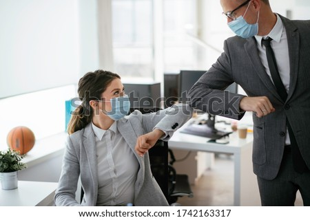Businessman and businesswoman with medical mask in office. Greetings in Covid-19 time. #1742163317