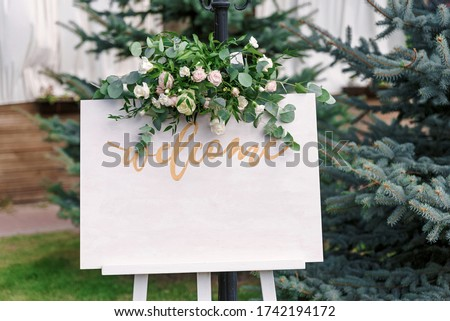 Wedding white Board Mockup easel with welcome sign decorataed with flowers, outdors. Greeting card template
