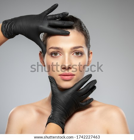 Doctor checks a skin before plastic surgery.  Face skin check before plastic surgery. Beautician touching woman face.Beauty treatments. Plastic surgery doctor is touching face of a patient by hands #1742227463