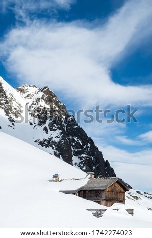 A beautiful vertical picture of an old wooden cabin in the snow against a great mountain