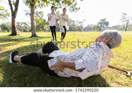 Senior woman is holding her hip,severe pain in her muscle,broken bone,injury to the waist,old elderly lying on the ground,she fell down while strolling,daughter,granddaughter ran to help grandmother Royalty-Free Stock Photo #1742290220