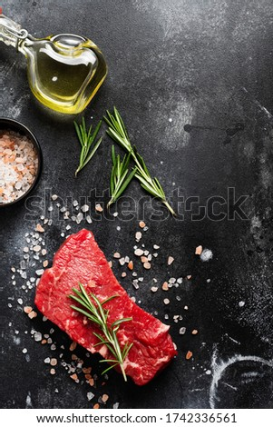Raw beef steak with spices, onions and rosemary on dark slate or concrete background. Top view