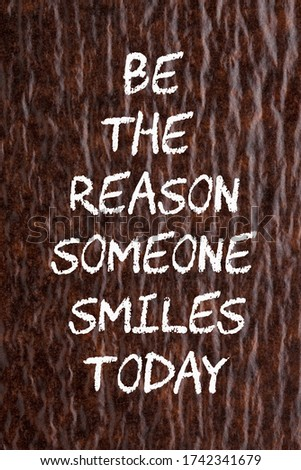 Be the reason someone smiles todaymotivation quote on wavy paper background.