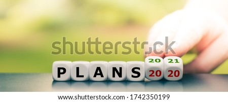 """Hand turns dice and changes the expression """"plans 2020"""" to """"plans 2021"""" Royalty-Free Stock Photo #1742350199"""