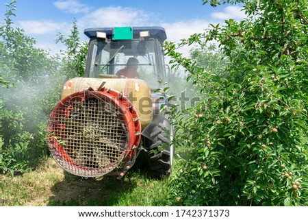 Tractor Sprays Pesticide in Apple Orchard - Spraying Mist Behind Tractor. Farmer Driving Tractor Through Apple Orchard. Apple Tree Spraying with a Tractor in Springtime. #1742371373