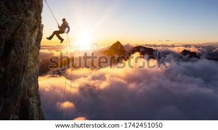 Epic Adventurous Extreme Sport Composite of Rock Climbing Man Rappelling from a Cliff. Mountain Landscape Background from British Columbia, Canada. Concept: Explore, Hike, Adventure, Lifestyle Royalty-Free Stock Photo #1742451050