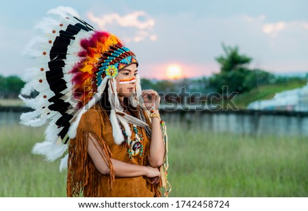 woman gets dressed up as native American Indian. She wears a feathered headdress and has a painted face. Indian woman hunter in concept Royalty-Free Stock Photo #1742458724