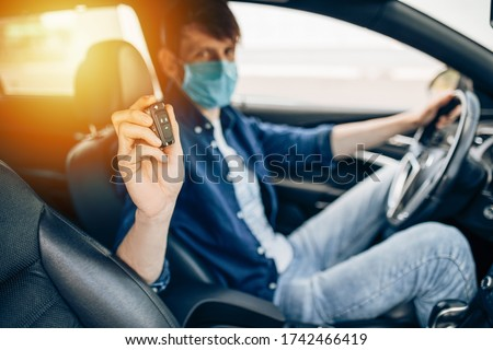 A young man in a medical protective mask buys a car, sits in the driver's seat at the wheel, checks the car at a car dealership and shows the car key. Quarantine, coronavirus #1742466419