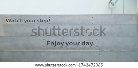 sign board word at stairs office. Enjoy Your Day - Watch Your Step - sign printed on the staircase with modernize decorative style. climbing stairs and Ambitions concept