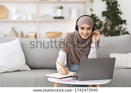 Online Education For Muslim Women. Happy Arabic Girl In Headscarf And Headset Studying With Laptop At Home, Taking Notes While Watching Webinar Royalty-Free Stock Photo #1742473940