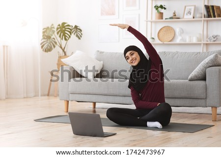 Home sport for muslim women. Smiling arabic girl in hijab practicing online yoga, watching video tutorial on laptop, excersising in living room Royalty-Free Stock Photo #1742473967