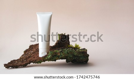 White plastic tube with facial moisturizer cream or facial cleanser on tree bark on beige background with copy space. Concept bio organic beauty products with natural extract and vitamin Royalty-Free Stock Photo #1742475746