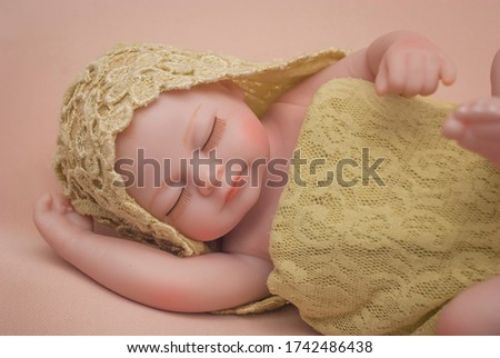 Newborn baby mannequin close up with simple wrapping technique with hoodie for posing and practicing newborn photography. khaki background and light green wrap