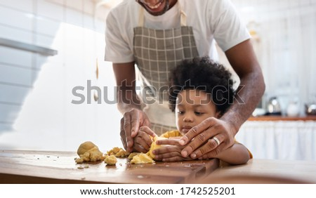 Black family having fun prepare bakery together at home. African American father and adorable son kneading dough in kitchen. Happy loving Man and little helper boy enjoy while making cakes and cookies Royalty-Free Stock Photo #1742525201