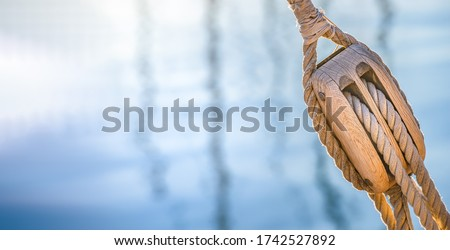 Sailing boat pulley, block and tackle with nautical rope. Nautic water panoramic background.  Royalty-Free Stock Photo #1742527892