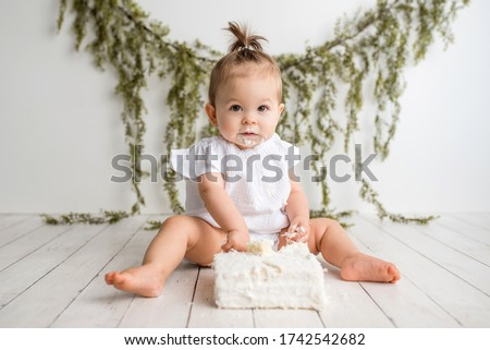 Baby girl first birthday cake smash on a white wood set in a white background and white cake Royalty-Free Stock Photo #1742542682