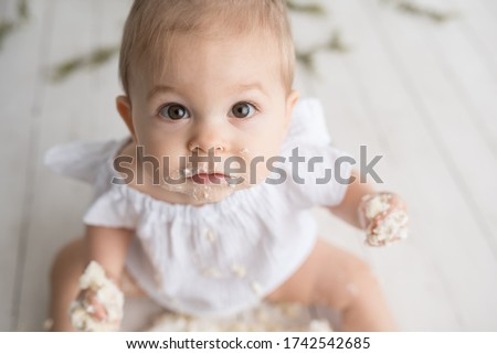 Baby girl first birthday cake smash on a white wood set in a white background and white cake Royalty-Free Stock Photo #1742542685