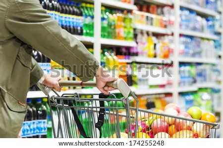man pushing a shopping cart in the supermarket. Royalty-Free Stock Photo #174255248