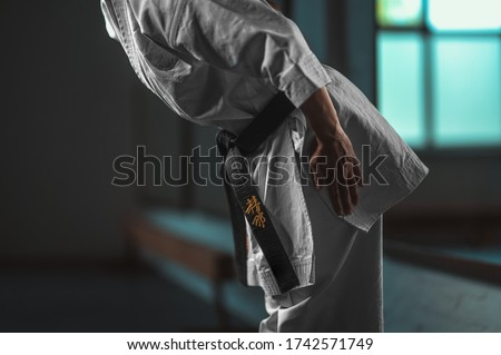 """Close Up Karate girl with black belt displaying respect - on belt Kaishin wich means """"Open Mind"""" Royalty-Free Stock Photo #1742571749"""