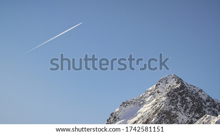 Plane flying with blue skies in a sunny day above a mountain peak of Austrian Alps during winter #1742581151