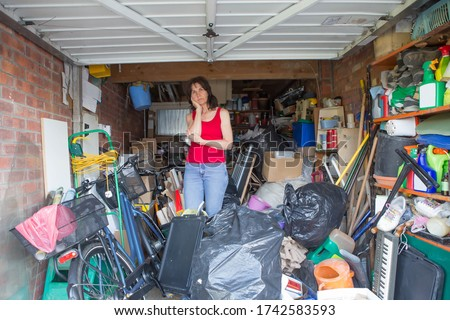Woman looking bemused about where to start in clearing out her garage Royalty-Free Stock Photo #1742583593
