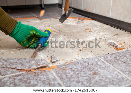dismantling of tile. Hands in green working gloves undermine the tile with a chisel and a hammer Royalty-Free Stock Photo #1742615087