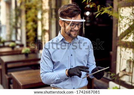 Happy waiter using digital tablet while wearing visor and protective gloves at outdoor cafe.  #1742687081