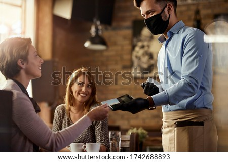 Young waiter wearing protective face mask while his guests are making contactless payment with credit card in a cafe.  #1742688893