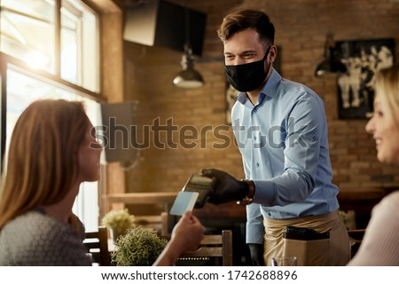 Female customer making contactless payment to a waiter who is wearing protective face mask in a cafe.  #1742688896