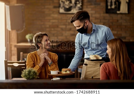 Young waiter wearing protective face mask while serving food to his guests in a restaurant.  #1742688911