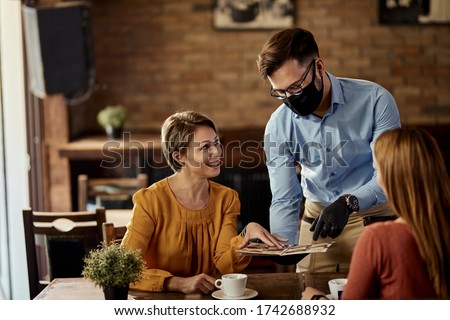 Waiter wearing protective face mask while recommending something from the menu to his customers. #1742688932