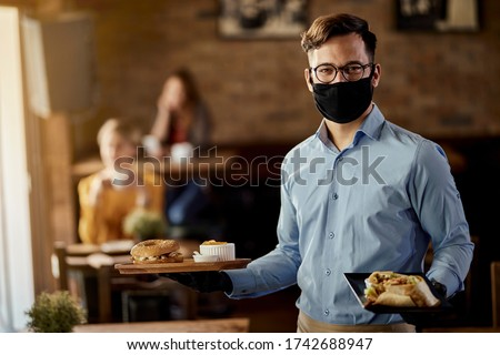 Young happy waiter wearing protective face mask while serving food in a restaurant.  #1742688947