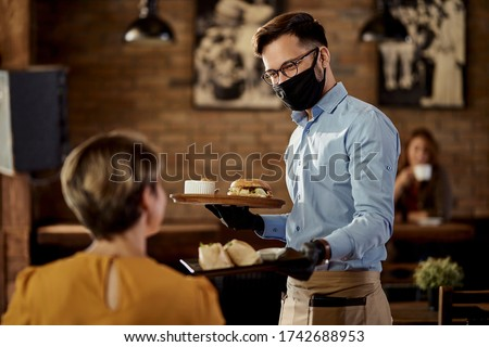 Happy waiter wearing protective face mask and gloves while bringing food to a customer in a pub.  #1742688953