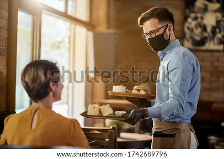 Happy waiter serving food to a guest while wearing protective face mask and gloves in a pub.  #1742689796