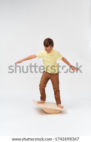 little boy stands on a special simulator for training the vestibular apparatus. to keep the balance standing on the treadmill. training of the vestibular apparatus.balance exercise balancing #1742698367