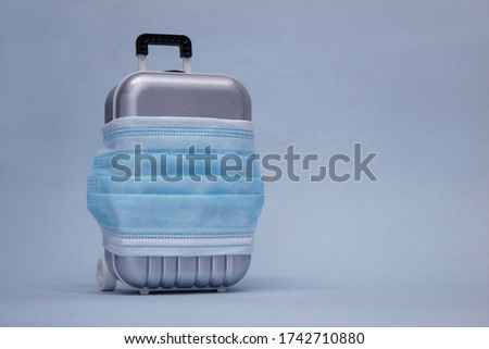 Time to travel. The concept of safe rest during a pandemic Covid-19 Coronavirus. Suitcase for travel with a medical mask Royalty-Free Stock Photo #1742710880