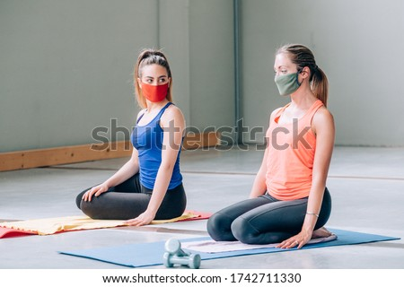 Two beautiful girls doing yoga for relax with protective masks in a gym with sports clothes - Quiet meditation in the face of a virus epidemic - Training during quarantine in the gym #1742711330