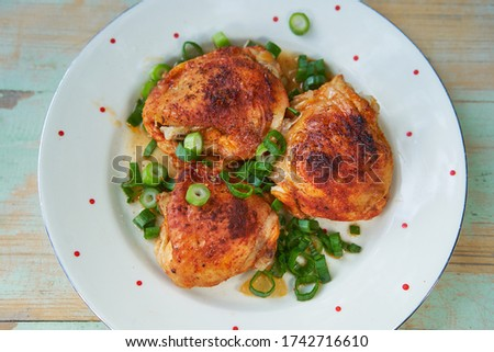 Close up Picture of vintage porcelain plate with roasted hot spicy chicken legs and chopped spring onion. Simple but tasty and juicy delicious light dish, with balanced nutritions and rich in protein.