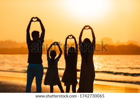 Family of four on the beach at sunset in United Arab Emirates .