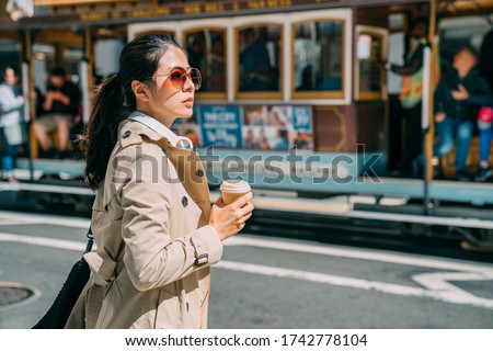 Young woman standing on street drinking coffee to go while putting headphones on neck. beautiful elegant female commuter waiting for taxi on road. blurred view driving cable car in san francisco back #1742778104