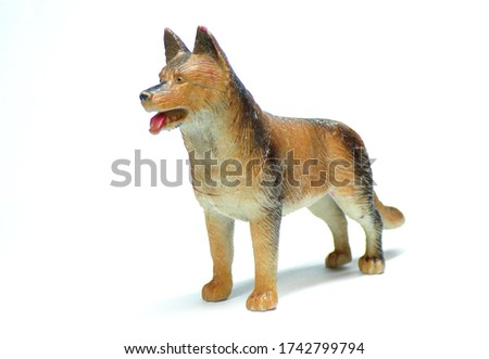 Figure of a dog on a white background. Statuette of a German shepherd isolated on a white background. Isolate with shadow. Copy of the dog. Models of pedigreed dogs.