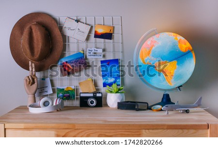 Modern home office workplace with inspirational printed photos on the mood board near glowing Earth globe. Map, retro camera, compass, hat, headphones, airplane model on the wooden table.