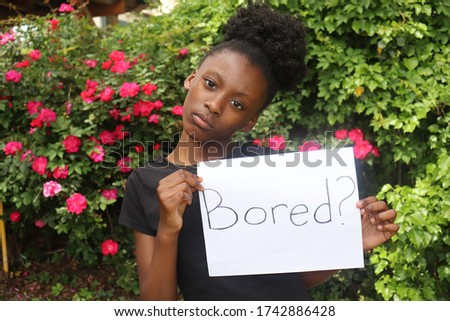 Girl holding white paper sign with the word Bored written on it