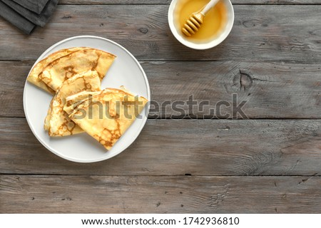 Crepes (Blini) on wooden background, top view, copy space. Homemade recipe of thin crepes for breakfast or dessert.  Royalty-Free Stock Photo #1742936810
