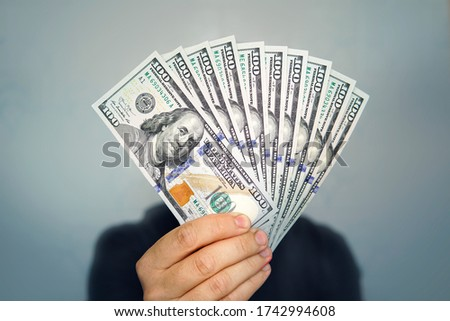 Hands holding dollar cash. 1000 dollars in 100 bills in a man's hand close-up on a dark background. Royalty-Free Stock Photo #1742994608