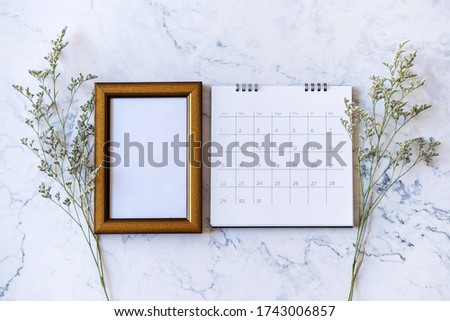 Picture frame and calendar and Caspia flower on marble background