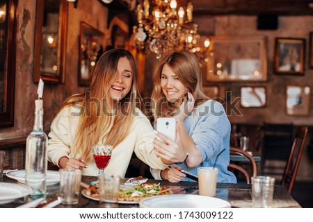 funny meeting of two friends after quarantine in a restaurant, girls exchange good news and take selfie on the phone. selfie time