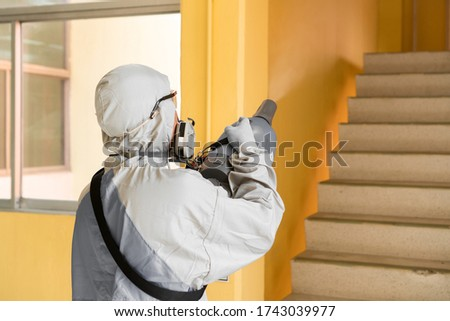 Sanitize office for covid 19 virus disease. Specialist in hazmat suit disinfecting coronavirus epidemic in office, prevention against Coronavirus disease 2019. Chemical spray at workstation area. Royalty-Free Stock Photo #1743039977