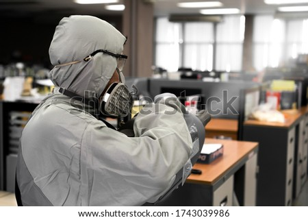 Sanitize office for covid 19 virus disease. Specialist in hazmat suit disinfecting coronavirus epidemic in office, prevention against Coronavirus disease 2019. Chemical spray at workstation area. Royalty-Free Stock Photo #1743039986